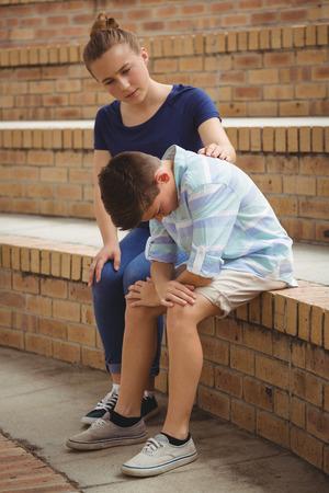 Colegial consolando a su triste amigo en los pasos en el campus de la escuela