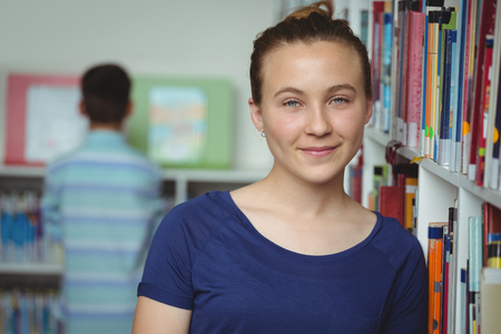 secondary school students: Portrait of smiling schoolgirl smiling in library at school