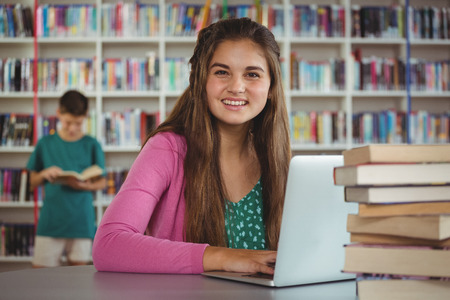 electronic book: Portrait of happy schoolgirl using laptop in library at school