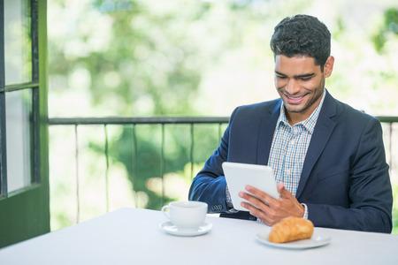 Smiling businessman using digital tablet in a restaurant