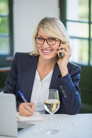 Portrait of businesswoman talking on mobile phone while writing on diary in a restaurant