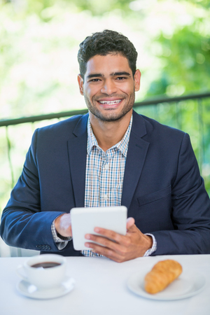 Portrait of happy businessman holding digital tablet in a restaurant Stock Photo