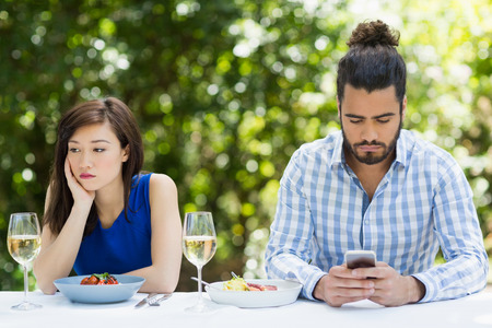 Man ignoring woman and using mobile phone in a restaurant