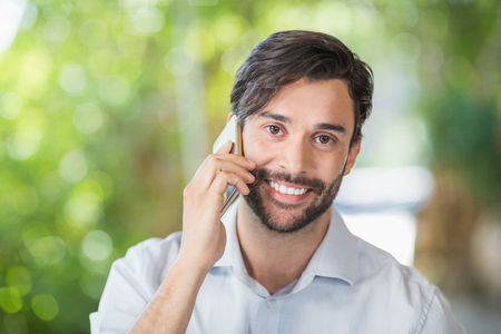Portrait of man smiling while talking on his mobile phone