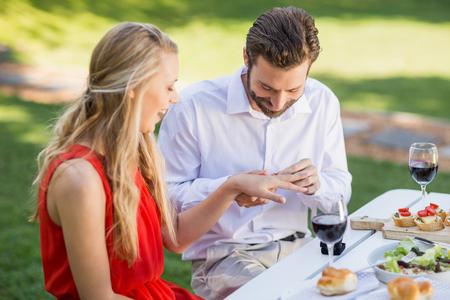 Glücklicher Mann, der einen Ring auf den Finger der Frau im Restaurant setzt