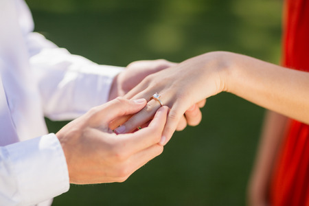 Close-up of man putting a ring on womans finger in the restaurant Stock Photo