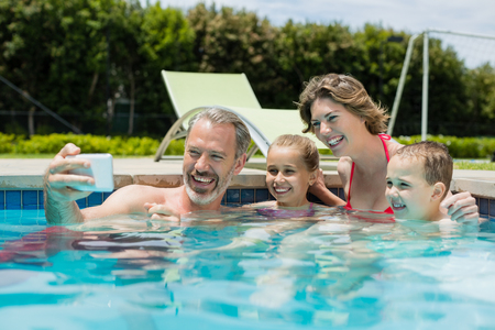 Man taking selfie with family in swimming pool Stock Photo
