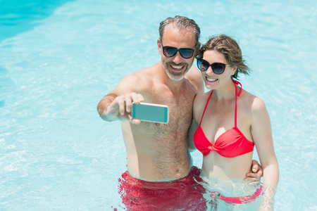 Happy couple taking selfie from mobile phone in pool on a sunny day Stock Photo