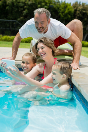 Woman taking selfie with family in swimming pool Stock Photo