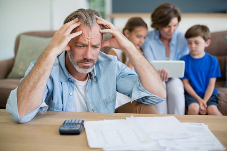 figuring: Worried man calculating bills in living room at home Stock Photo