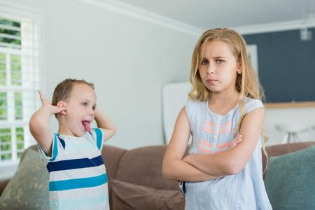 Broer plaagde zijn zus terwijl hij met gekruiste armen in de woonkamer thuis stond Stockfoto