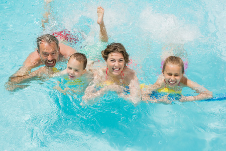 Portrait of happy parents and kids having fun in pool on a sunny day Stock Photo