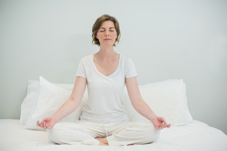 Woman doing meditation on bed in bedroom at home Stock Photo