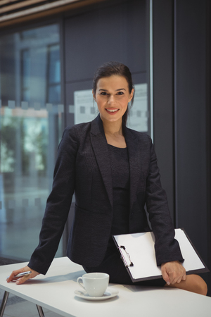 Portrait of businesswoman with clipboard sitting on the desk at office Stock Photo