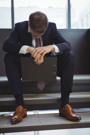 Depressed businessman with clipboard sitting on stairs at office Stock Photo