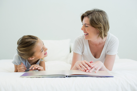 Smiling mother and daughter lying on bed and reading book in bedroom at home Stock Photo