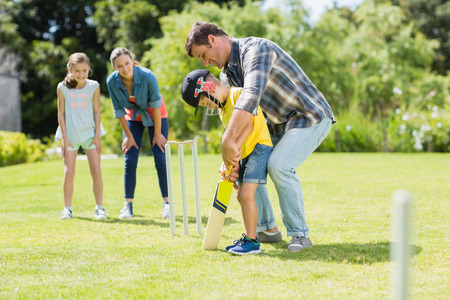 Happy family playing cricket together in backyard Stock Photo