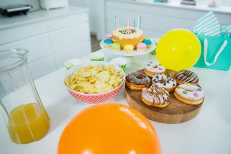 Doughnuts, potato chip, birthday cake and balloons on table in kitchen Stock Photo