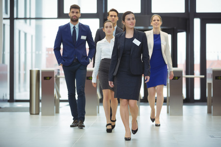 Businesspeople walking in a lobby at office