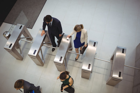 Top view of business executives passing through turnstile gate Banco de Imagens - 73693017