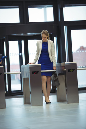 Businesswoman passing through turnstile gate at office