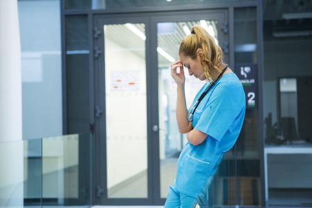 Upset female doctor standing in corridor at hospital Stock Photo