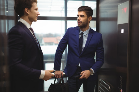Businessmen interacting with each other in elevator of office 版權商用圖片