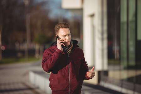 Male executive talking on mobile phone in office premises LANG_EVOIMAGES