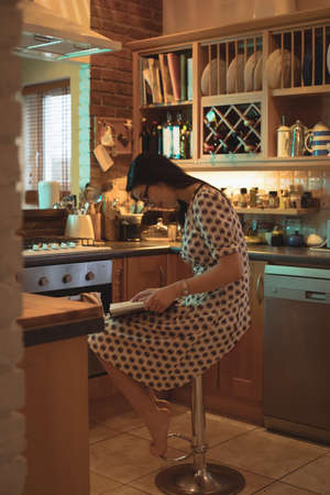 turning the page: Woman reading a book in kitchen at home