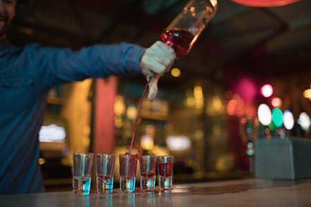 hotel staff: Bartender pouring alcoholic drink in shot glasses at bar LANG_EVOIMAGES
