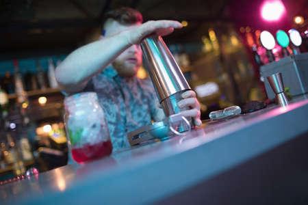 hotel staff: Bartender preparing cocktail at counter in bar LANG_EVOIMAGES