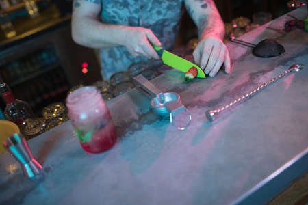 hotel staff: Bartender cutting strawberry for preparing cocktail at counter in bar