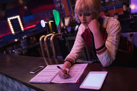hotel staff: Female bartender using digital tablet while maintaining records at the counter in bar