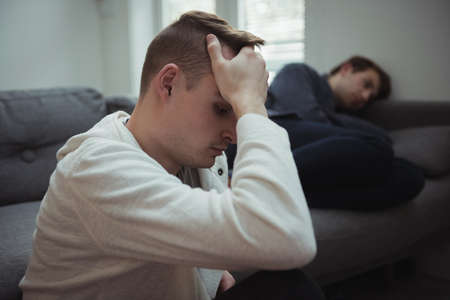 couple on couch: Upset gay couple ignoring each other at home