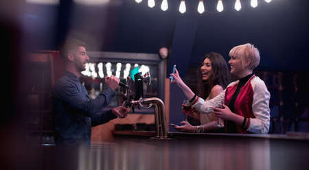 hotel staff: Bartender interacting with beautiful women at counter in bar