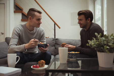 couple on couch: Gay couple having breakfast together at home LANG_EVOIMAGES