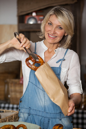 Female staff packing sweet food in paper bag at supermarket