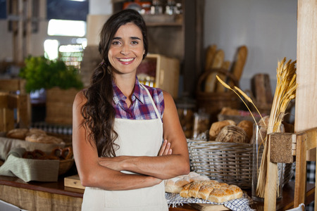 Portrait of smiling female staff standing with arms crossed at bakery shop in supermarket
