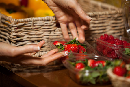 wicker work: Hands of female staff holding bowl of strawberries in supermarket Stock Photo