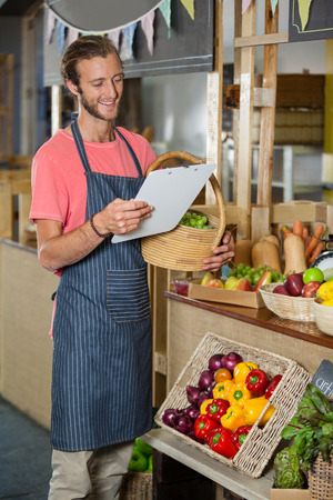 Male staff looking at clipboard in organic section of supermarket Stock Photo