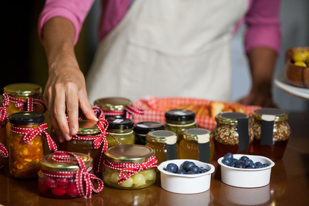 Mid-section of staff arranging jar at counter in market