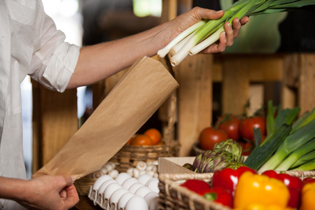 Staff packing spring onion in paper bag at grocery shop at supermarket