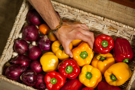 wicker work: Hand of male staff selecting bell pepper in organic section of supermarket Stock Photo
