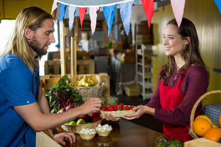 wicker work: Smiling female staff offering strawberry to customer at organic section in market Stock Photo