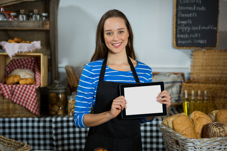 wicker work: Smiling female staff using digital tablet at counter in bakery shop