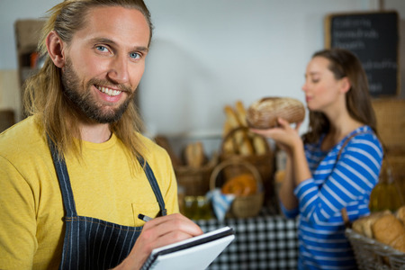 wicker work: Smiling male staff writing on notepad at counter in bakery shop