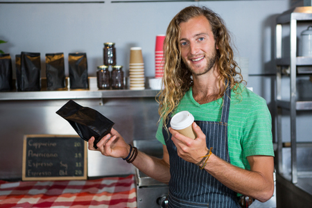 Portrait of male staff holding coffee cup and parcel bag at counter in coffee shop Stock Photo