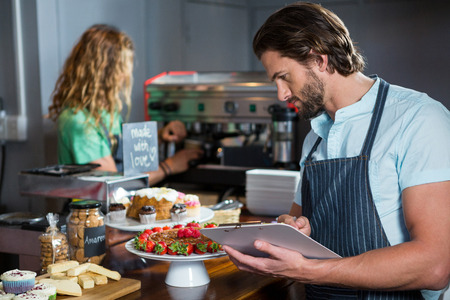 Male staff maintaining a record on clipboard at counter in coffee shop