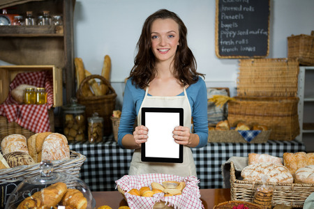 wicker work: Portrait of smiling staff showing digital tablet at bakery counter in market