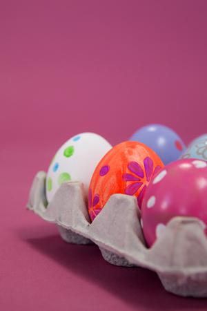 Colorful Easter eggs in egg carton on pink background